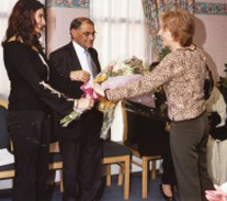 Sabina Gatrad presenting  Mrs Gatrad with flowers on behalf of the Manor Hospital at the OBE celebration.